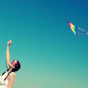Young woman flying kite