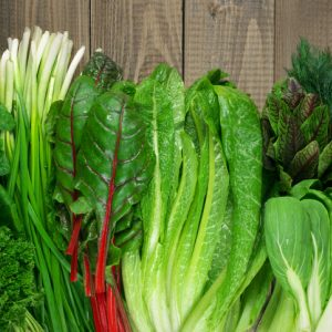 A variety of fresh leafy greens and herbs on wood table