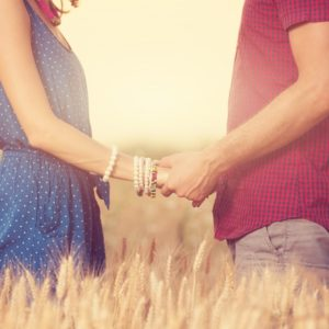 Couple holding hands in field