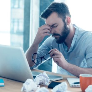 Man frustrated at work considers spiritual meaning of inflammation