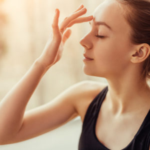 Woman touching third eye on forehead