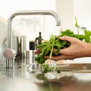 Woman washing greens at sink