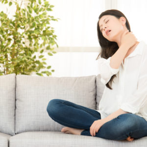 Woman with neck pain sitting on couch holding neck