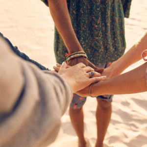 Hands together on beach