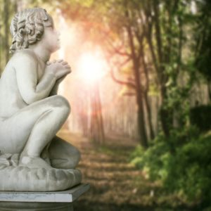 Cherub statue in forest with sun