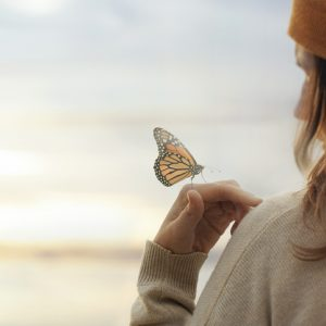 Woman with butterfly on her hand to symbolize contact your spirit guide