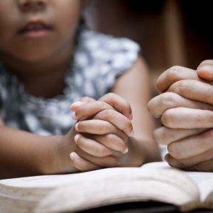 Child with folded hands on bible