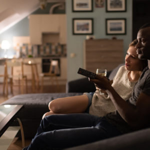 Couple watching a movie or TV show at home on couch, with bottle of wine.