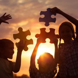 Kids and puzzle pieces at sunset