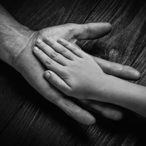 Hands of elderly man holding younger hand