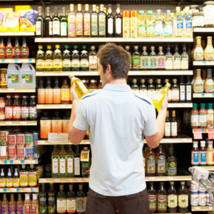 Man comparing food labels at grocery store