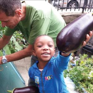 Girl with eggplant in garden