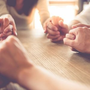 Grieving women holding hands