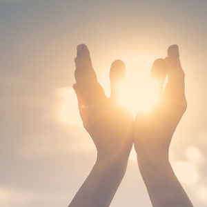 Persons hand holding sun in palm feeling energized. Spiritual, mind, body concept.