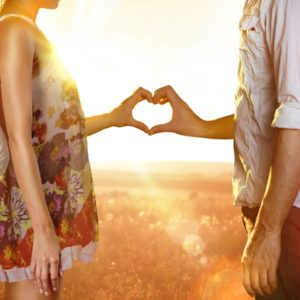 Couple creating heart with hands in field