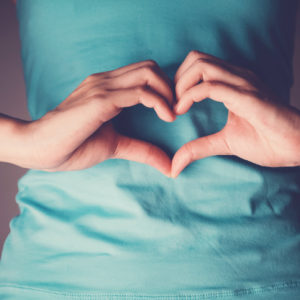 Heart hands over stomach to signify gut health