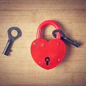 Image of heart lock and key on wood
