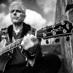 Jai Uttal Strums Guitar black and white photo