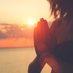Silhouette of woman's hands in prayer