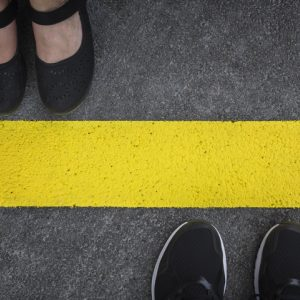 Two pairs of shoes on opposite sides of yellow line to symbolize boundaries