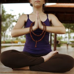Woman meditating with strand of mala beads