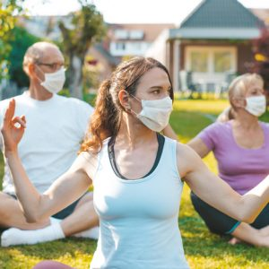masked retreat goers do yoga