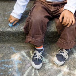 Boy drawing on sidewalk with chalk