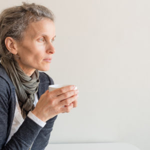 A pensive woman drinks coffee
