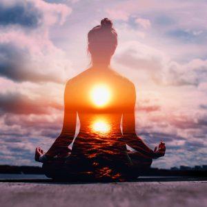 Woman meditating at sunrise awaken
