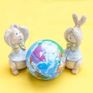 wooden rabbit toys looking at a wooden earth in shock for easter for animal lovers