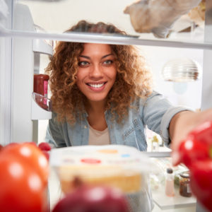 woman reaching into refrigerator to clean it out