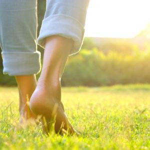 A woman walks on sunny grass
