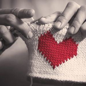 Woman knitting a heart for craftivism