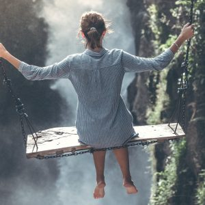 Woman on large wooden swing swinging over a waterfall