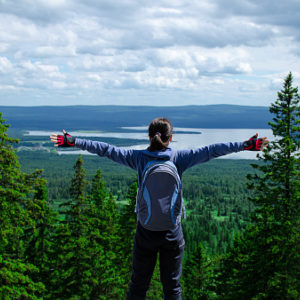 Woman with backpack on in the woods, arms stretched toward the sky