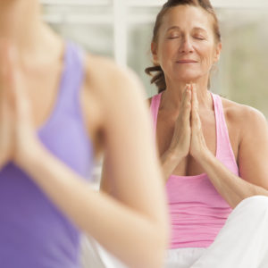 woman centering herself in a yoga class by meditating