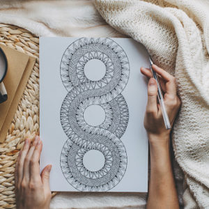 A woman's hand is drawing a mandala