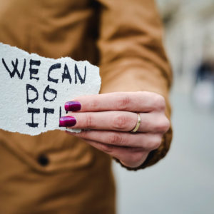 Woman holding We Can Do It sign