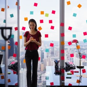 Woman in office with sticky notes