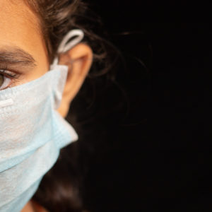 eyes of young girl child with medical mask wearing, protection against covid 19