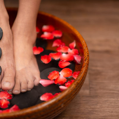 Beautiful female feet at spa soaking for foot care