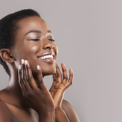 Happy woman touching soft smooth skin on her face to signify the body as sacred