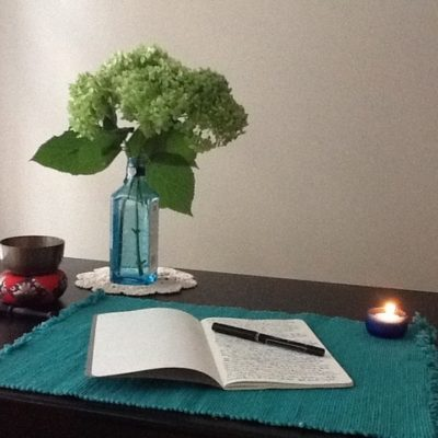 journal lays open on table with lit candle