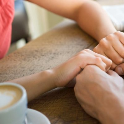 Man and woman holding hands with coffee