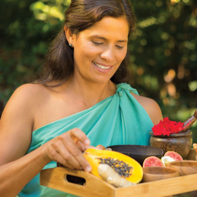 Jeana Naluai holding tray filled with various fruit and bowls