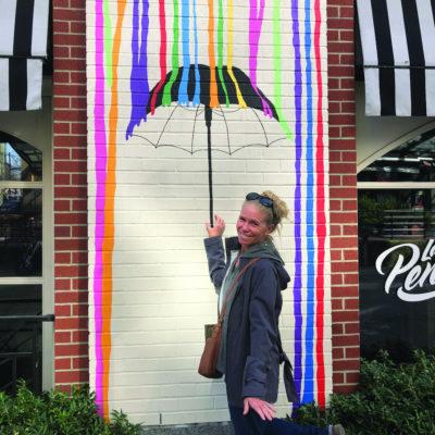 Kalia Kelmenson standing in front of a mural of an umbrella