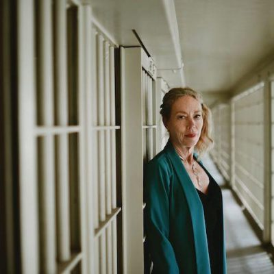 Dr. Karen Gedney standing in front of prison bars