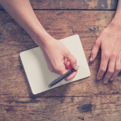 Person writing in journal on wood table