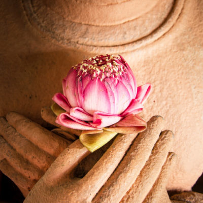 Sandstone Buddha with lotus blossom in hands
