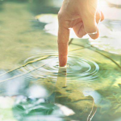 Pointer finger creating circular ripples in a pond illustrates centering prayer